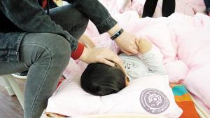 ▲特教老师正在安抚患有睡眠障碍的孩子入睡。