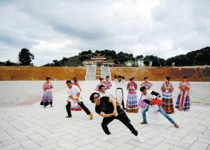 杨明示范如何跳改编版的苗族迎宾舞和芦笙舞。