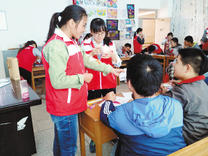 志愿者教小同学折纸船。