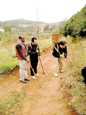 苏年春带着儿子和外国徒弟采药。受访者供图