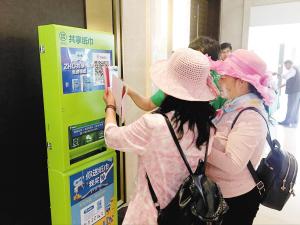 市民在使用共享纸巾机取纸。