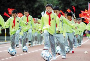 官渡学生展示足球技巧。记者周密摄