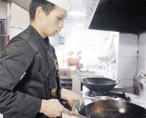 厨师李师傅在高温炉火前炒菜。 记者杜文蕾摄