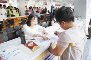 残疾人在招聘点前填写表格。记者赵伟摄