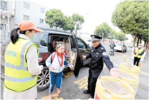 安全护学队在校门外维持秩序。官渡区委政法委供图